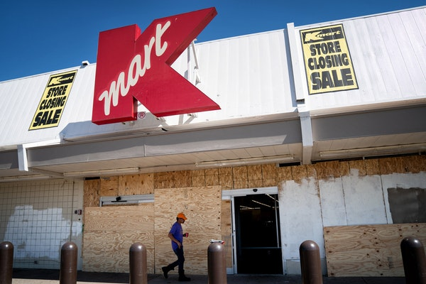 Employees took a break Wednesday from cleaning up damage from riots and looting at the Kmart store on E. Lake Street in Minneapolis. It will not reope