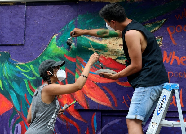 Local artist Leslie Barlow, left, and Ryan Stopera painted a mural on the boarded-up front of Fall Out Arts Initiative in Minneapolis' Whittier neig