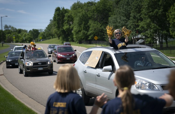 Glendale Elementary School teacher Karla Schutz waved to students who lined streets in their neighborhoods as staffers drove down the streets of Savag