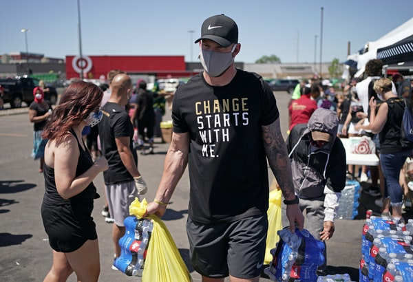 Kyle Rudolph helps a woman carry items to her car during a food distribution event last Friday in Minneapolis.
