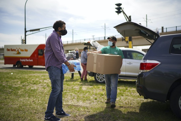 Fran Evenson, left, and Chris Knutson carried a load of water and blankets for residents of a homeless encampment near the Sabo bridge.