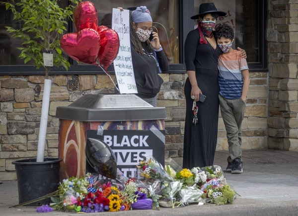 """""""It's devastating,"""" said Zola Richardson as she held her son Gabriel 11, close as she stood to pay respect near the site where a middle-aged black man"""