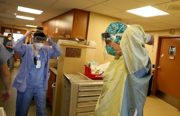 Healthcare workers don PPE before phoning a COVID-19 patient in an ICU at St. Paul's Bethesda Hospital in May 7.