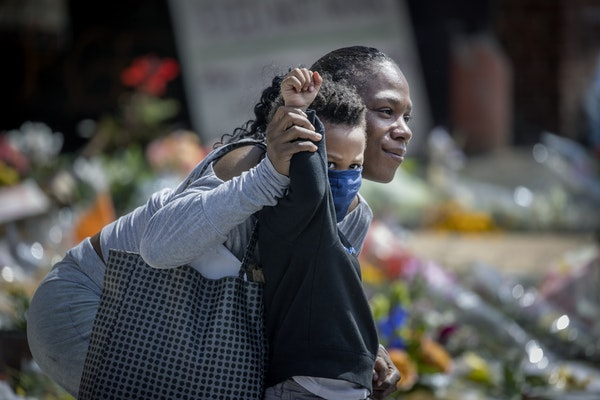 Karnisha Johnson, held her 3-year-old son's Drew Anderson's arm up in support of Terrence Floyd, the brother of George Floyd, as he arrived to the sce