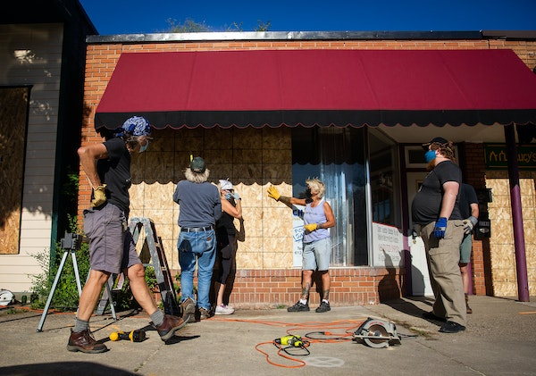 Kore Grate, center, the owner of Five Element Martial Arts, helps to board up a neighboring business just north of E. 38th Street and Cedar Avenue S.