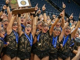 Eastview high kick dance team members celebrate after receiving their championship trophy on Feb. 15, 2020 at Target Center.