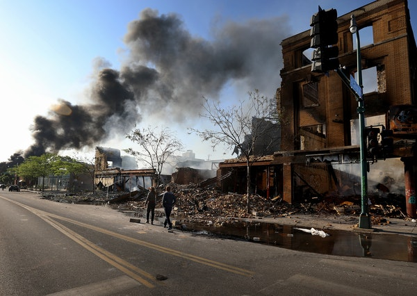 People survey the damage along Lake St. near S. 27th Ave. as a fire burns to the east Saturday, May 30, 2020, in Minneapolis, MN.] DAVID JOLES • dav