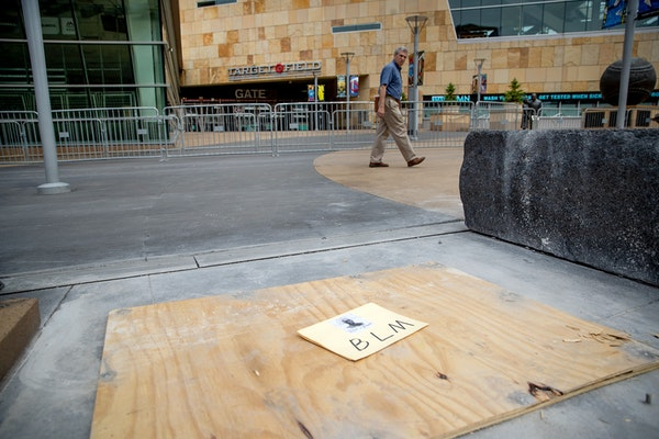 A passerby looks back where a statue of former Twins owner Calvin Griffith stood outside Target Field