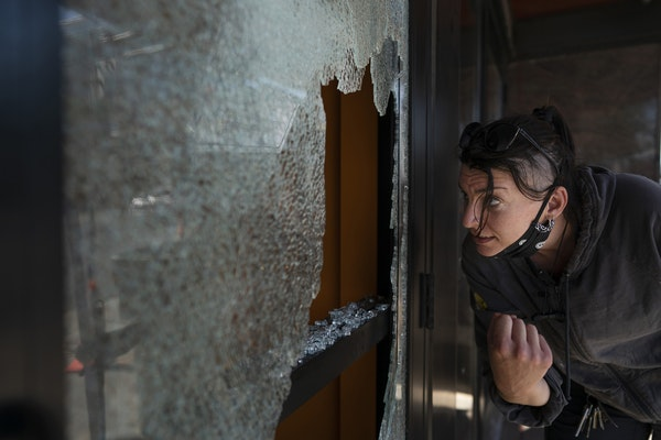 Megan Culverhouse, an employee at the John Fluevog shoe store in Uptown, cleaned up broken glass from a window hit by gunfire from an early morning sh