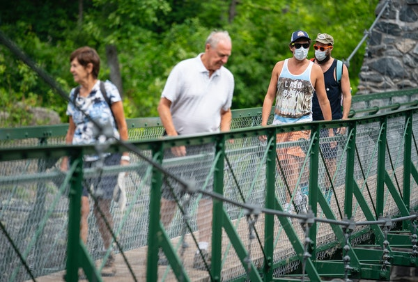 (From left) Patsy and Warren Thieve from Bloomington crossed the swinging bridge while being followed by their son-in-law David Turley and his husband