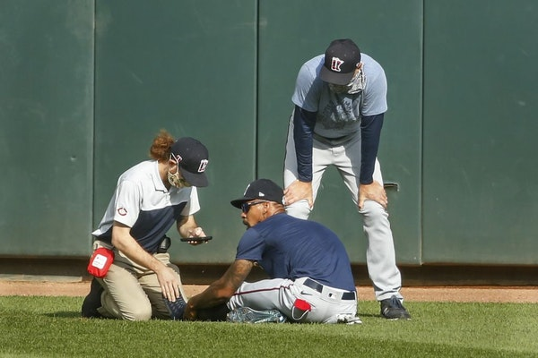 Byron Buxton, center, holds his ankle after he stumbled during an intrasquad game on Monday. He received attention from assistant athletic trainer Mat