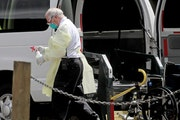 A hospital worker held a bottle of disinfectant outside the North Ridge Health and Rehab nursing home in New Hope, Minn. The nursing home previously e