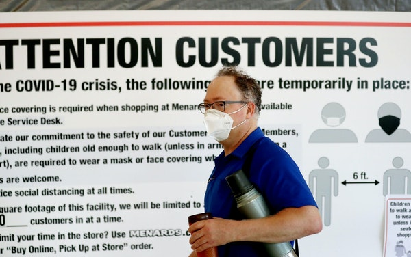 An employee walks by a sign alerting shoppers to the COVID-19 protocol at Menards in Maplewood recently. [Credit: DAVID JOLES, Star Tribune]
