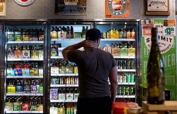 Ryan Youngdale stands in front of the beer fridge at Stinson Wine, Beer, and Spirits. ] COURTNEY PEDROZA ¥ courtney.pedroza@startribune.com July 2, 2