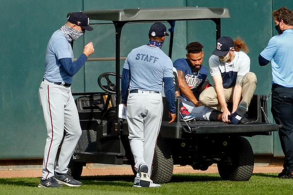 (From left) Twins manager Rocco Baldelli and coach Tony Diaz watched as assistant athletic trainer Matt Biancuzzo steadied the ankle of center fielder