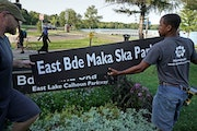 Minneapolis Park and Recreation Board (MPRB) workers install new placards changing East and West Lake Calhoun Parkways to East and West Bde Maka Ska P