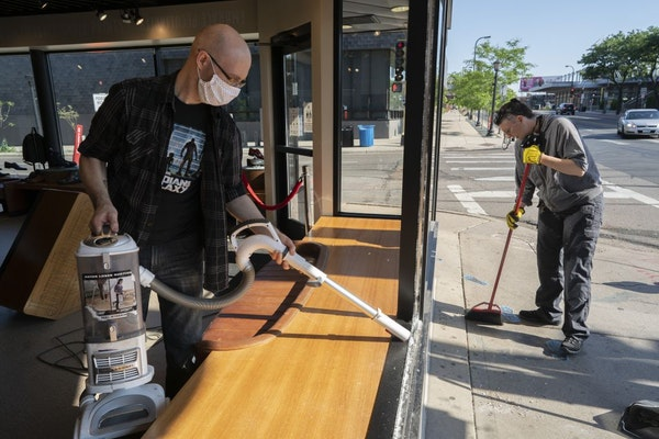 Jeff Neppl, left, and Megan Culverhouse, employees at John Fluevog shoe store in Uptown, cleaned up broken glass from a window that was hit by gunfire