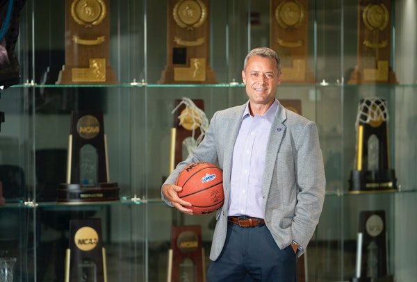 Athletic Director Phil Esten stood for a photo in front of the trophy case at the University of St. Thomas