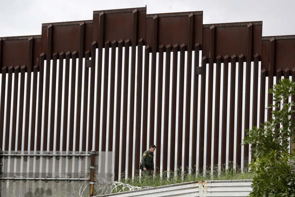 A border patrol agent walks along a border wall separating Tijuana, Mexico, from San Diego, in San Diego on March 18.
