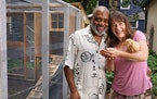 Classical musicians (and spouses) Bill Eddins and Jennifer Gerth with one of their chickens, Faye, near the elevated chicken coop and chicken run that