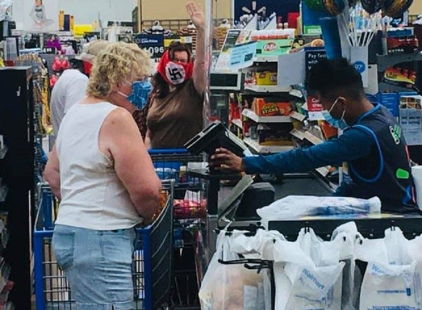 A couple wrapped in crude swastika masks shout and gesture defiantly from the back of the checkout line at a Wal-Mart in Marshall, Minn., on Saturday.