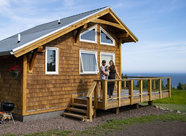 Andrew and Simone Strand held their 4-month-old son Eddie in front of their cabin in Grand Marais that they rent out as an Airbnb.
