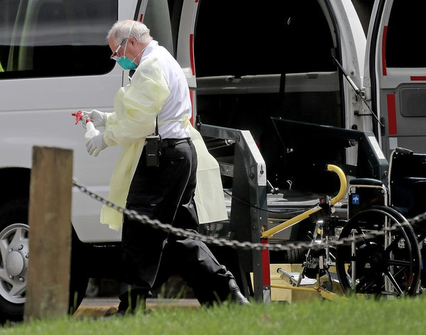 A worker with a bottle of disinfectant outside the North Ridge Health and Rehab nursing home in New Hope in July.
