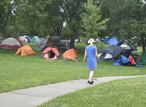 A visitor walked a path by tents at a homeless encampment at Powderhorn Park in Minneapolis on Thursday. There are about 300 tents at Powderhorn Park.