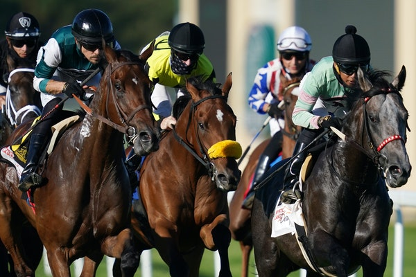 Jockey Jareth Loveberry, center in mask, rode Summer Assault to victory in the Mystic Lake Derby at Canterbury Park.