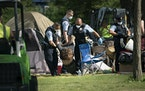 Police dragged a person from a tent as they cleared tents and possessions from the east side homeless encampment at Powderhorn Park in Minneapolis on
