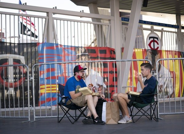 Luke Widbin and Nathan Heerts ate takeout outside Target Field while listening to the Twins home opener via phones.