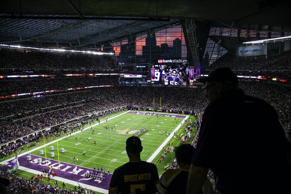 The sun sets behind a silhouette of the Minneapolis skyline as Vikings plays took the field during a game last season.