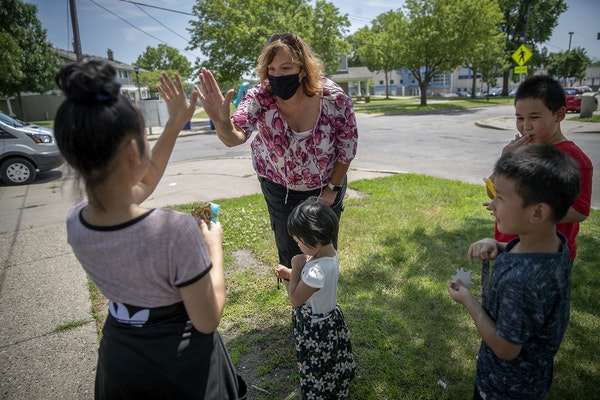 The Ramsey County Sheriff's outreach Cmdr. Mary Kay Skelly gave air high-fives to children after giving them freezes and stickers in the McDonough Hom