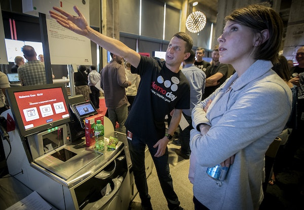 """Matthew Howard, a lead project owner, showed visitors the """"Self-Checkout,"""" at Target's science fair type event introducing innovation-related projects"""