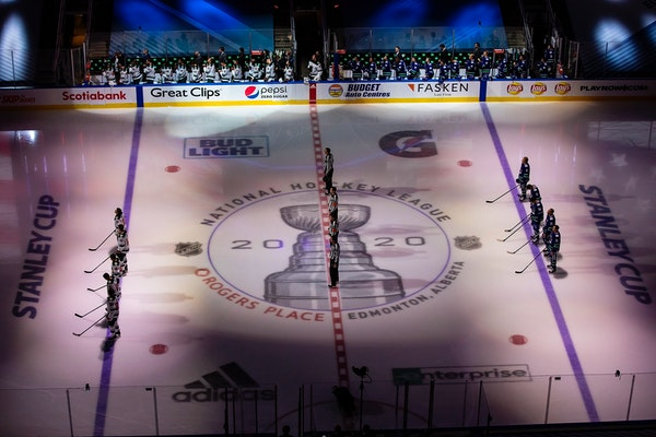 The Canucks and Wild stand for the national anthems before Game 1 of the series in Edmonton.