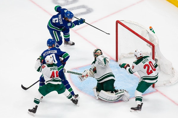 Wild goaltender Alex Stalock can't stop Vancouver's Brock Boeser from scoring during the second period.