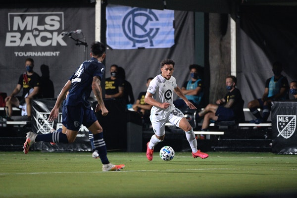Minnesota United midfielder Hassani Dotson controls a ball in front of Sporting Kansas City defender Roberto Puncec