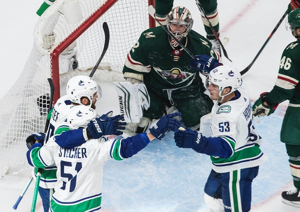 Wild goalie Alex Stalock watches as the Vancouver Canucks celebrate a goal during the second period