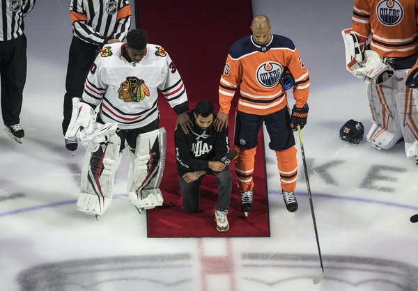 Matt Dumba took a knee during the U.S. national anthem on Saturday as he was flanked by Chicago's Malcolm Subban and Edmonton's Darnell Nurse, rig