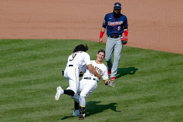 Pittsburgh's Kevin Newman, center, topples over as Cole Tucker celebrates in front of Twins left fielder Marwin Gonzalez, after Newman drove him and B
