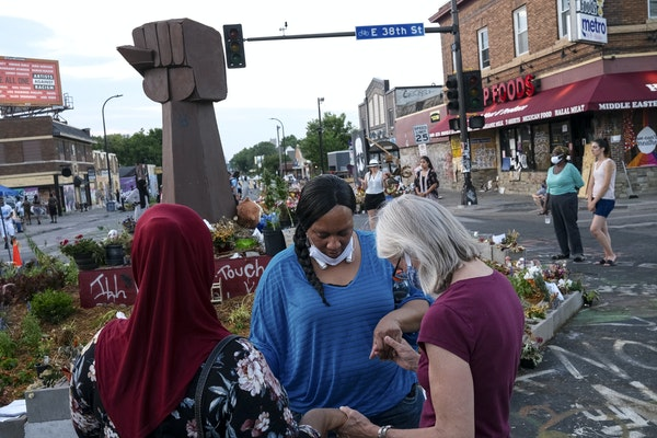 A prayer circle at 38th Street and S. Chicago Avenue in Minneapolis, the intersection where George Floyd was killed. Plans to reopen the area are begi
