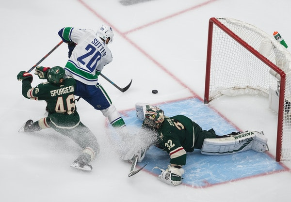 Wild goalie Alex Stalock makes the save on Vancouver's Brandon Sutter as Jared Spurgeon defends during the third period Friday night.
