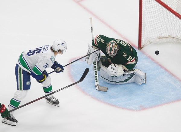 Wild goalie Alex Stalock (32) is scored on by Vancouver Canucks' Antoine Roussel (26) during the third period