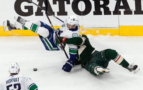 The Wild's Joel Eriksson Ek, right, hauled down Vancouver's Loui Eriksson for one of 11 Minnesota penalties in Game 3.