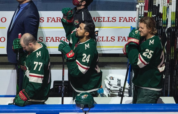 The Wild's Matt Dumba stands with fist raised during the national anthem before taking on the Canucks on Thursday night.