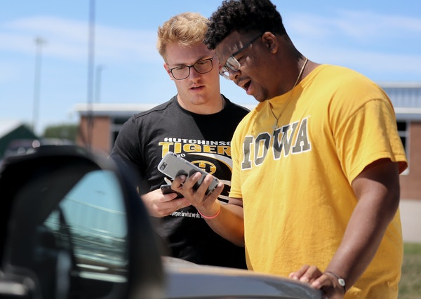 Hutchinson football players Ty Glaser, left, and Jordan Titus monitor their phones while waiting to hear how the MSHSL would vote on the upcoming foot