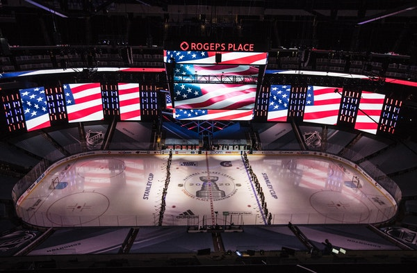 Colorado Avalanche and Minnesota Wild players stand for the national anthem during an exhibition game in Edmonton