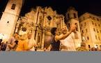 Minnesota Orchestra violin player Deborah Serafini dances with trumpet player Manny Laureano in the Plaza de la Catedral in Havana, Cuba, on May 14, 2