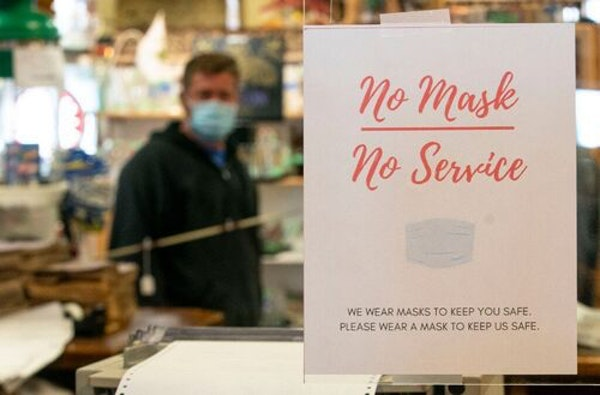 FILE-Father Time Antiques in Duluth has posted signs requiring masks outside and inside their store. The St. Louis County Board voted Tuesday to send