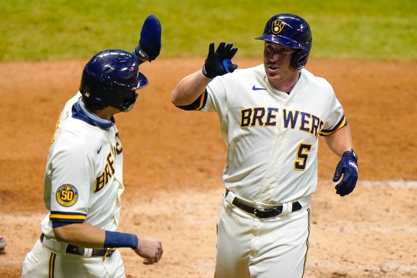 Milwaukee's Jedd Gyorko is congratulated by Christian Yelich after hitting a two-run home run during the eighth inning